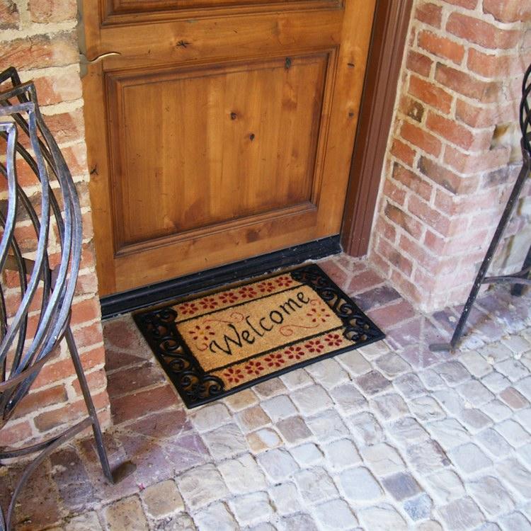 Welcome home doormat outside of a wooden door
