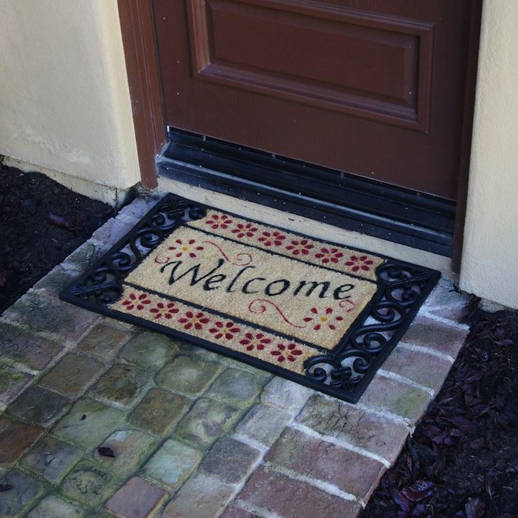 Welcome home Coir DoorMat outside of a door