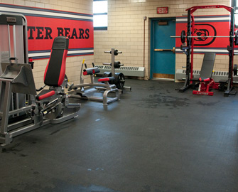 Z cycle flooring under weight machines at a school gym.
