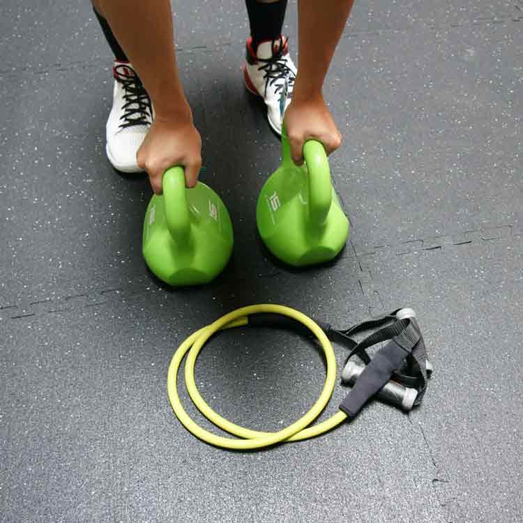 Person with hands on green kettlebells ready to exercise on Z-Cycle floor
