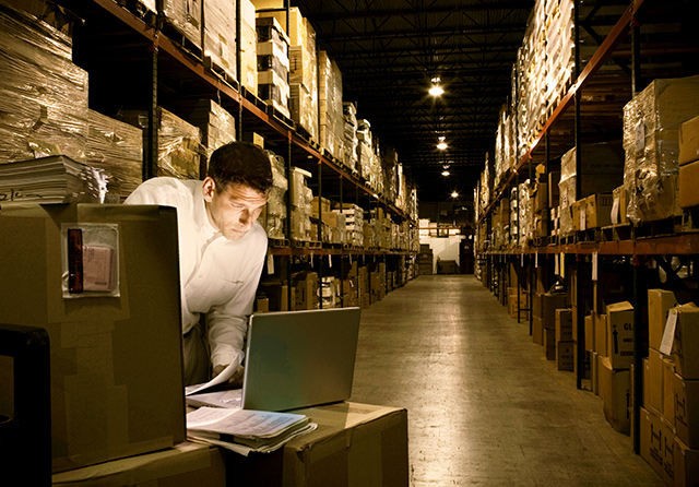 A full warehouse with a single employee, working from his laptop atop a stack of boxes.