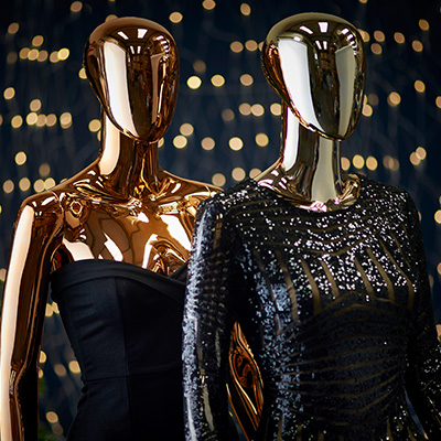Golden mannequins wearing very formal clothes.