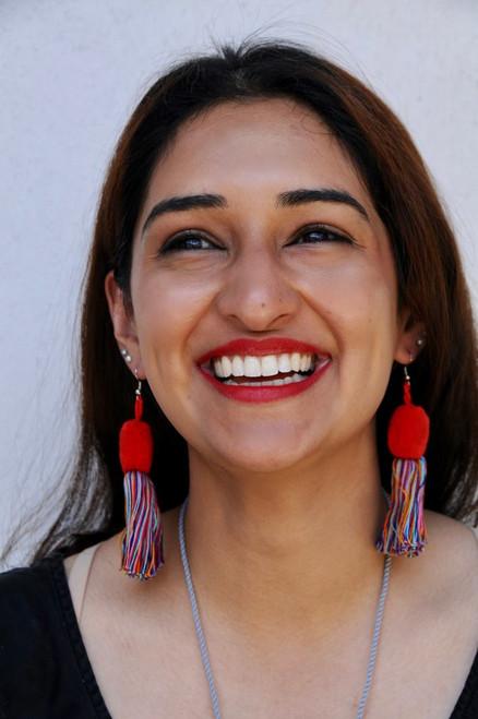 Pom with tassel earrings on model