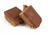 A layer of freshly roasted and salted pecan pieces, topped with our own soft and buttery caramel with creamy milk chocolate spread over the top.