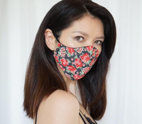 An Asian woman with mid-length hair wears a red floral face mask by Sainted Sisters