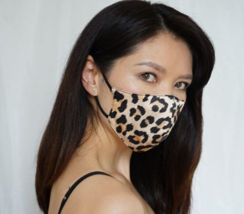 A woman wears an animal print mask