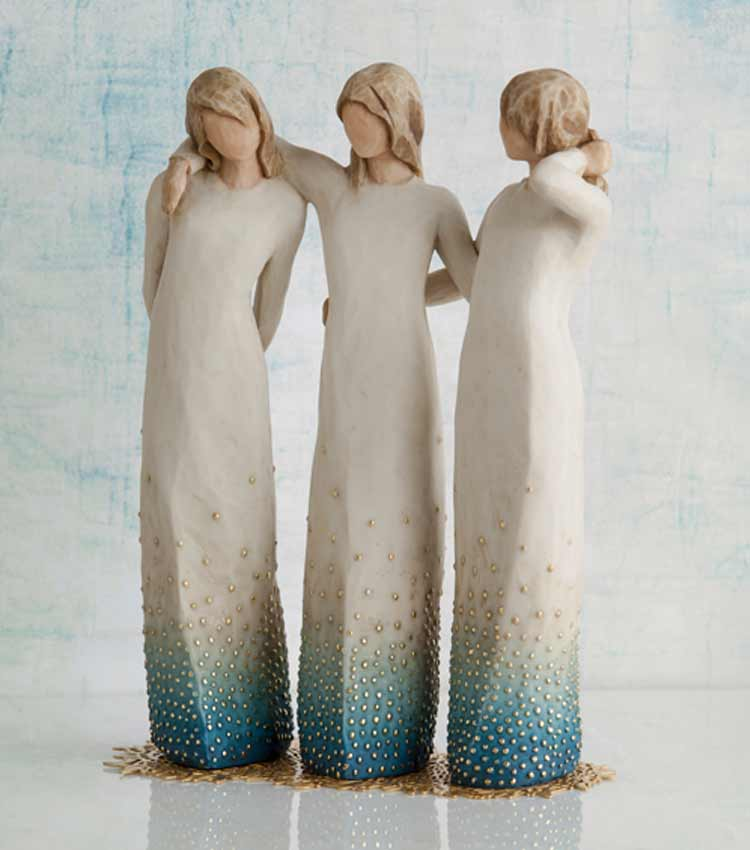 Hand-carved figurine of three women with their arms around each other