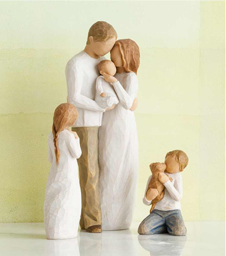 Hand-carved figurines of family with mom, dad, baby, girl, and boy holding dog