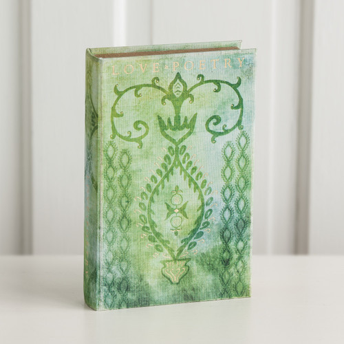 Green/blue book with swirl designs standing up on white surface