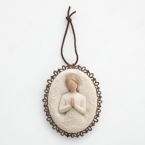 Round wooden outline cream pendant with image of faceless woman figurine praying in white dress