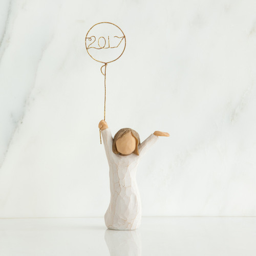 Small girl figurine wearing white dress and holding gold 2017 balloon up