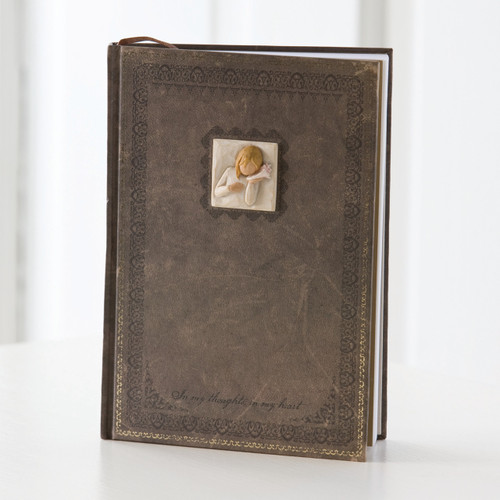Standing brown book with square pendant of little girl figurine in cream colors on the top center of book