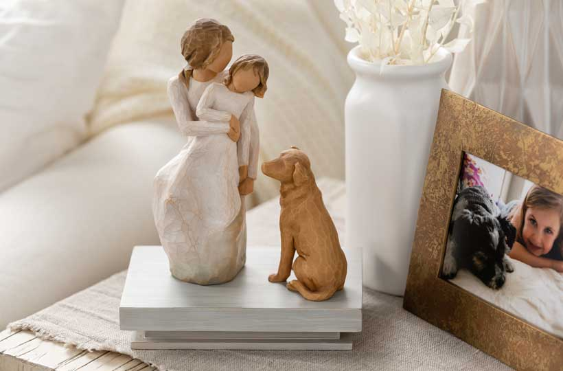 Hand carved figurine of a mother and daughter and a yellow lab dog sitting on a hand-painted shelf on a table