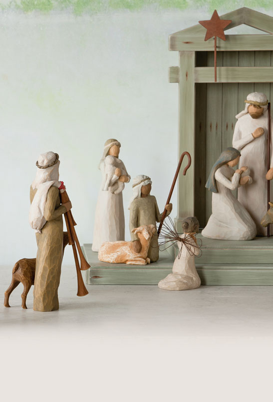 Hand carved figurines of a the nativity. Shepherd approaching Mary, Joseph and baby Jesus