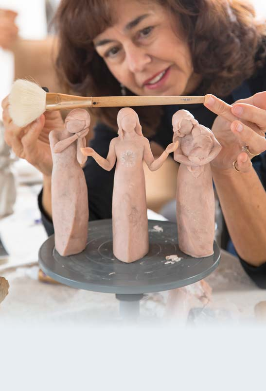 Arist holding paintbrush above three female figurines sculpted from clay