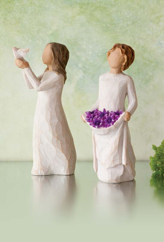 Hand-carved figurines of girl holding dove and girl holding purple flowers