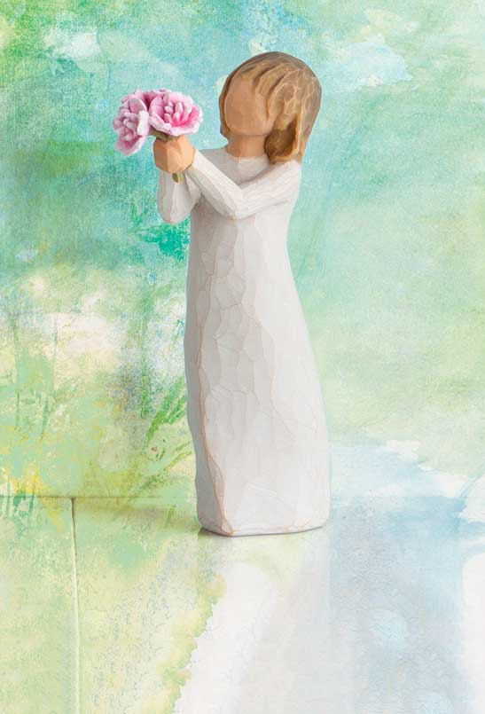 Hand-carved figurine of girl holding a handful of pink peony flowers
