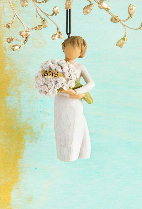Hand-carved figure ornament hanging from gold tree holding bouquet of white flowers with 2019 carved into gold ribbon in flowers