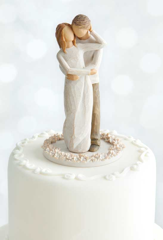 Hand-carved figurine of a man and woman on top of a wedding cake