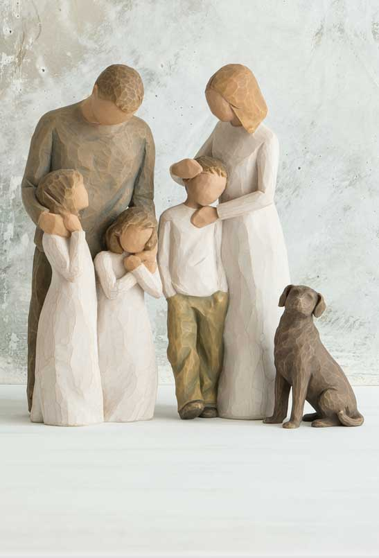 figure grouping with man, woman and three children all standing up holding each other next to dark colored dog sitting on ground by them