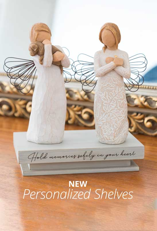 Angel figurines displayed on a shelf with engraved words Hold memories safely in your heart