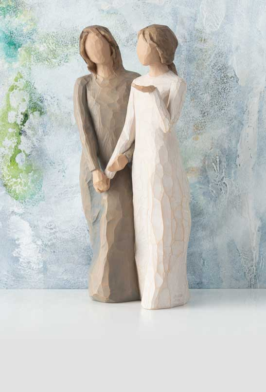Hand-carved figurine of two women walking and holding hands
