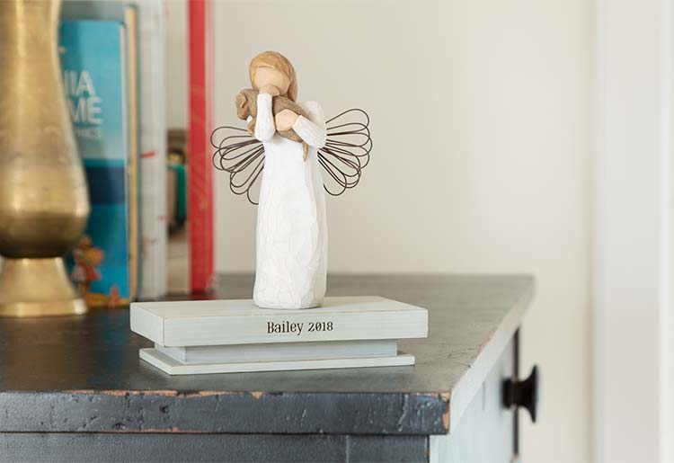 standing angel figure with wire wings holding dog stop shelf reading Bailey 2018