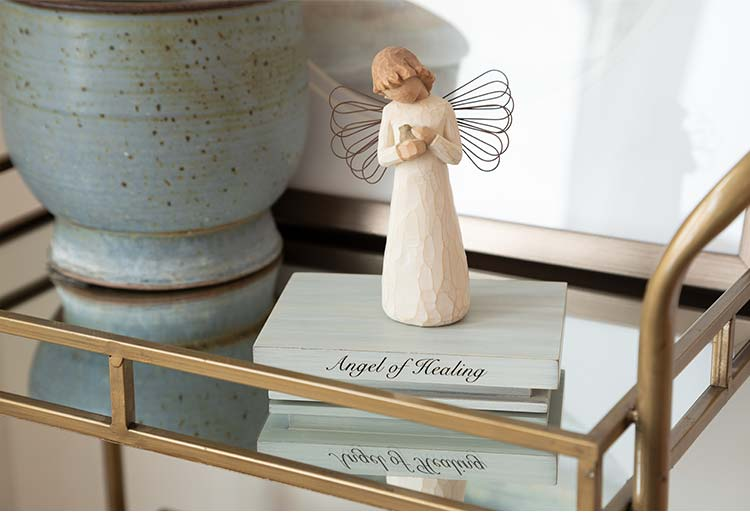 standing angel figure with wire wings holding bird to chest atop shelf reading Angel of Healing