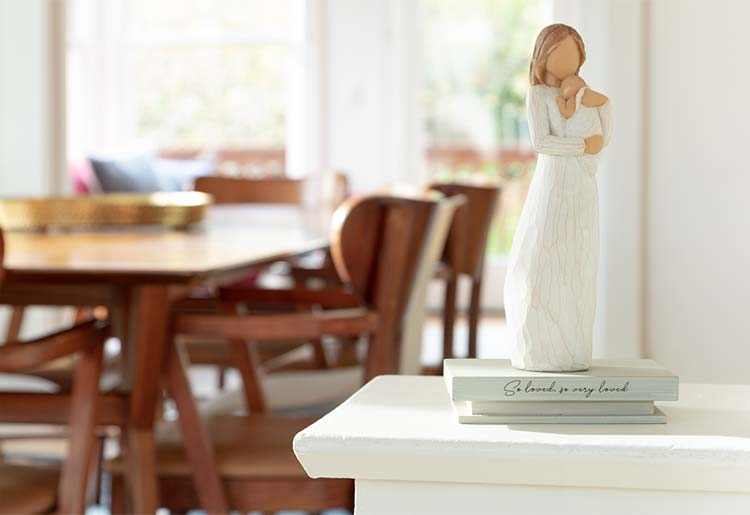 standing female figure holding baby atop shelf that reads So loved, so very loved