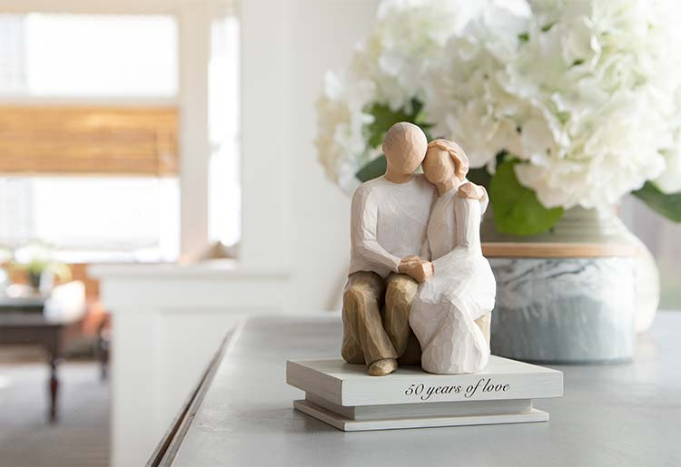female and male figures sitting on rock embracing each other atop a shelf reading 50 years of love