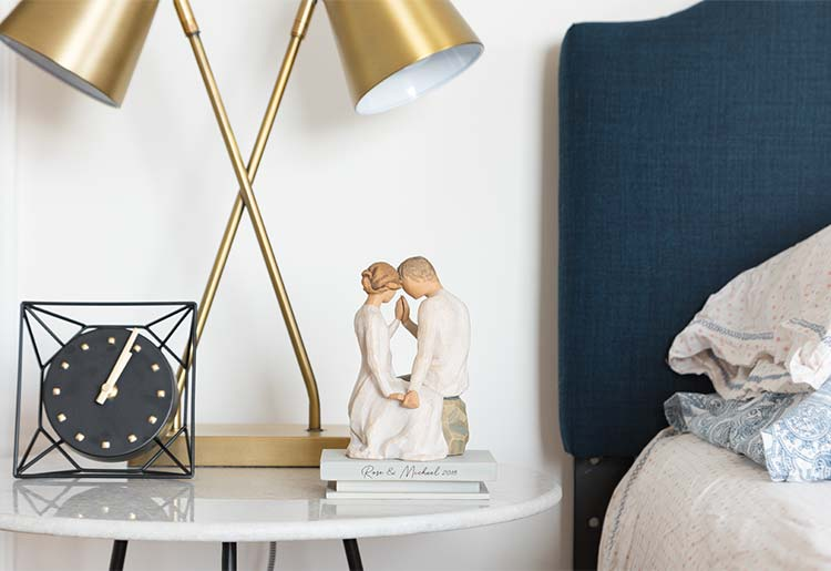 male and female figures sitting on rock faced towards each other and touching foreheads and hands atop shelf that reads Rose & Michael 2018