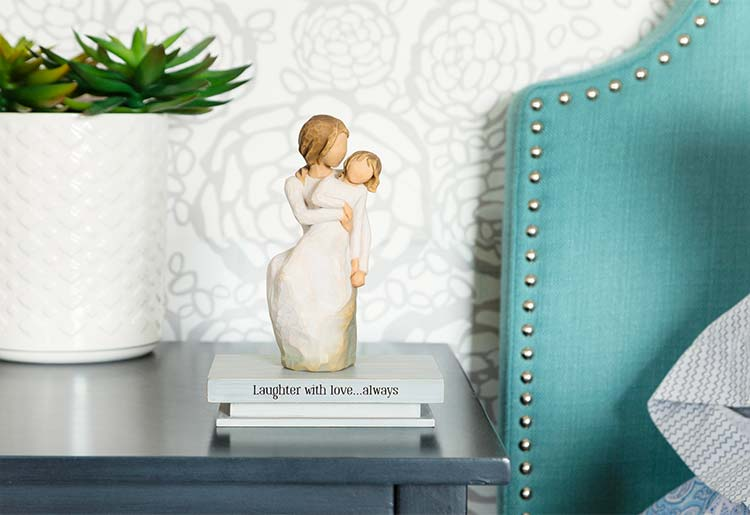 girl sitting on mother's lap atop shelf that reads Laughter with love... always