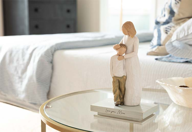 standing female figure hugging head of standing boy figure atop shelf that reads Love you, Mom