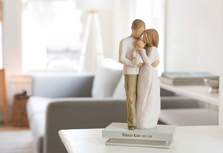 male and female figures standign and holding a newborn baby figure atop shelf that reads Hanna Kate 10.1.18
