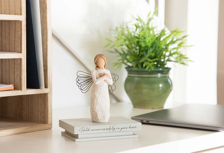 standing angel with organic carvings on dress and hands crossed over heart atop shelf that reads Hold memories safely in your heart