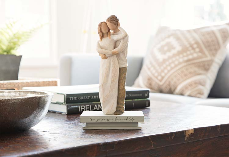 male and female figures standing and embracing atop shelf that reads true partners in love and life