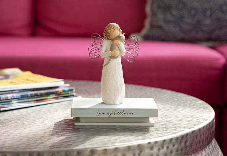 standing angel with wire wings holding cat atop shelf that reads Love my little one