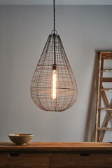 An open wire weave pendant in rust finish that creates visual interest while maintaining an open feel to the room. The design is inspired by cray fishing traps. Large