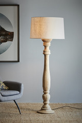 An elegant candlestick style turned wood floor lamp in natural mango wood, finished with a drum shade in light natural linen. Natural wood