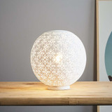 A round table lamp featuring a delicately-patterned, perforated matt white outer shell. When unlit the exterior shows the delicate perforations, when illuminated the light radiates out through the perforations.