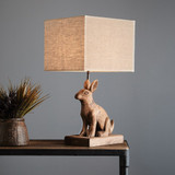 A charming carved wooden rabbit sitting on a beveled rectangular plinth supporting a square shade.