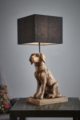 A friendly carved wooden dog sitting on a beveled rectangular plinth supporting a square shade. Lifestyle