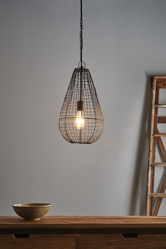 An open wire weave pendant in rust finish that creates visual interest while maintaining an open feel to the room. The design is inspired by cray fishing traps. Small