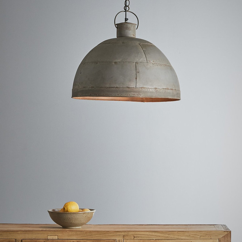 A riveted dome pendant in two rustic finishes. This pendant is designed to patina over time for a vintage aesthetic. Vintage grey