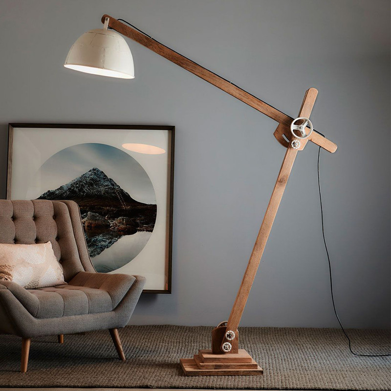 A large industrial style, articulated over-arch floor lamp in wood with chunky iron tightening wheels at the joints and a hand riveted iron shade in white.