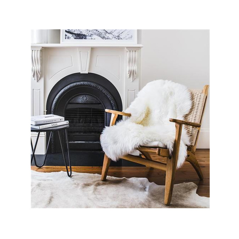 Our Merino Sheepskin in warm white exudes luxurious comfort. Use it as a deliciously soft throw on your favourite occasional armchair or sofa for the ultimate in comfort and style. Styled view.