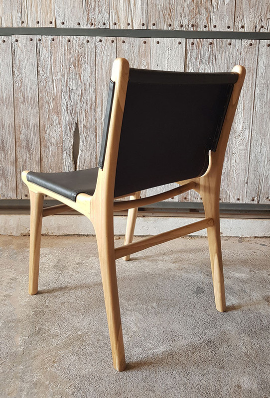 Teak dining chair with full sweep of black leather and a relaxing semi-reclining posture. Back view