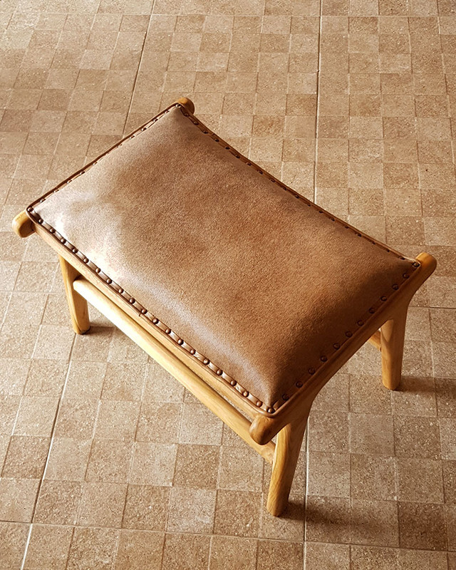 Matching cowhide and teak footstool that comes with the cowhide chair.