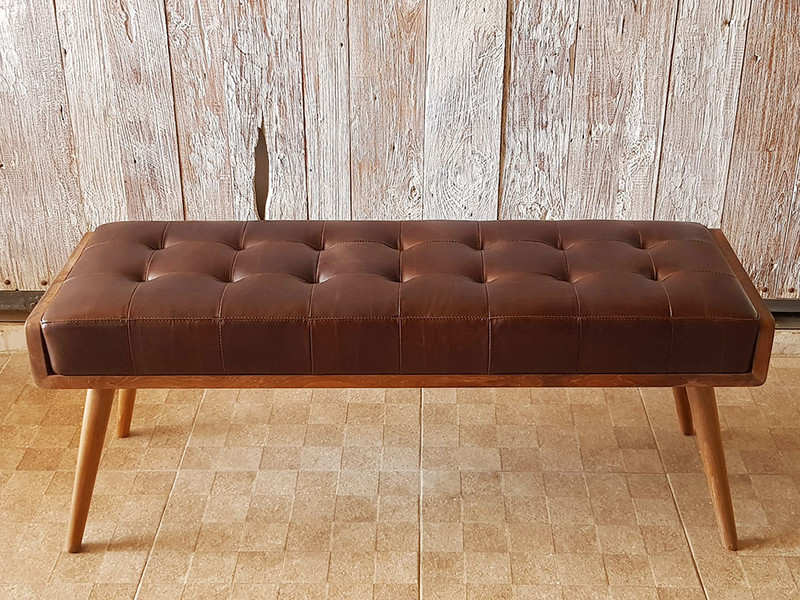 Luxurious and plush buttoned leather bench seat with solid teak frame. Front view