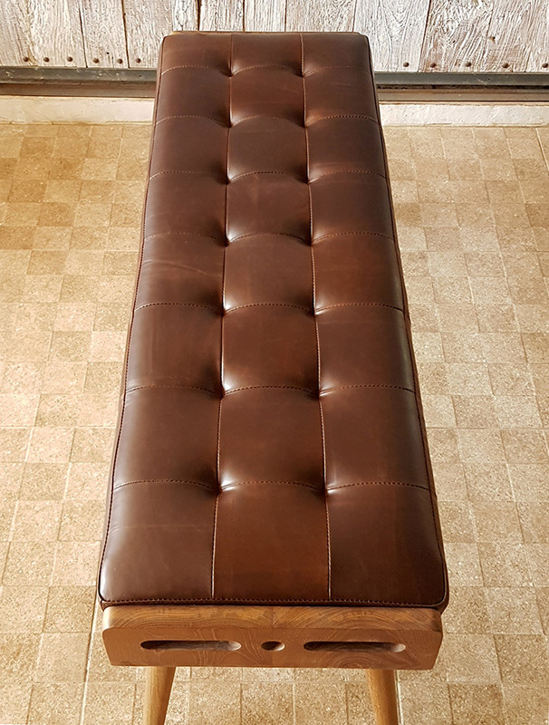 Luxurious and plush buttoned leather bench seat with solid teak frame. Side view from above